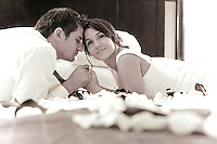 Silvia and Adrian lay on the rose petal-covered bed of their suite at the Hyatt Regency in Bellevue, WA after their wedding day. Just a short rest before heading to the after-party. (Photo by Andy Rogers/Red Box Pictures)