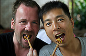 Johannes Strempel and Justin Jin enjoy coconut worms at the Dai Meng Mou Restaurant in Ruili, Yunnan province, southwestern China.