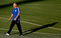 Brazil head coach Luiz Felipe Scolari casts a long shadow as he walks on the pitch during training ahead of tomorrow's World Cup quarter final vs Colombia