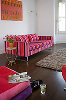 In the living room plain white walls are the perfect backdrop for a brightly coloured abstract painting and the bold pink and purple stripes of the Tricia Guild sofa