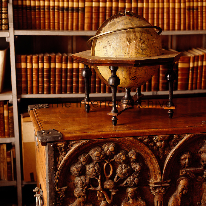 A detail of an antique globe on an ornately carved chest in the library