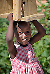 A girl carries her stool in Camp Corail, a controversial resettlement of earthquake survivors north of Port-au-Prince, Haiti. Thousands of families were relocated to Corail from flood-prone areas of the capital in 2010, yet the promises of jobs that lured them there failed to materialize.