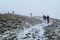 Hikers and snow on Little Man. The Lake District.