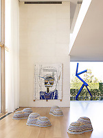 A group of sculptural stools by Christian Astuguevieille in the living room; a painting on boards and a bronze sculpture in the garden can be seen behind
