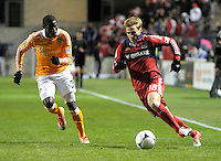 Chicago midfielder Chris Rolfe (18) races toward the Houston goal with Houston defender Kofi Sarkodie (8) in pursuit.  The Houston Dynamo defeated the Chicago Fire 2-1 in the Eastern Conference play-in game for the MLS Playoffs at Toyota Park in Bridgeview, IL on October 31, 2012.