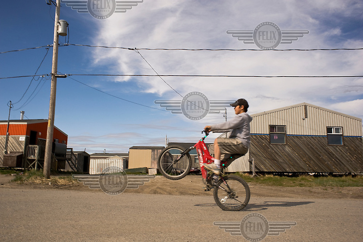 A boy pulls a wheelie on his bicycle as he rides along a street in the Inuit village of Kuujjuaq.
