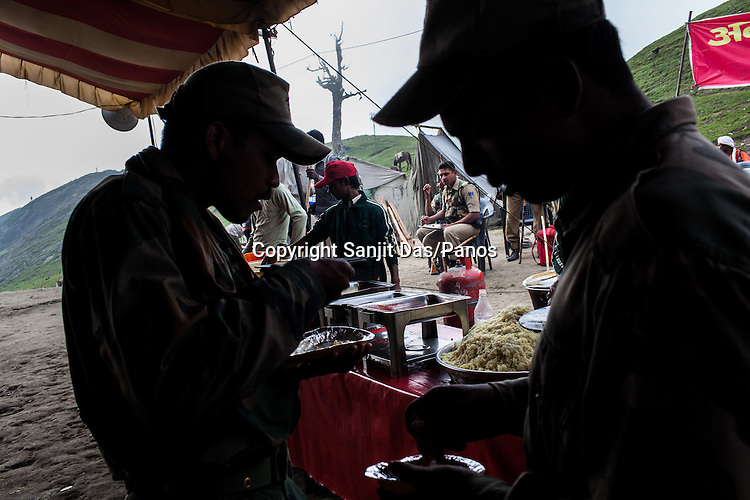 Hindu pilgrims and soldiers stop to eat a campsite providing free food to pilgrims at the first pass, Pissu Top (11500ft) enroute to the pilgrimage to Amarnath in Kashmir, India. Hindu pilgrims brave sub zero temperature and high latitude passes and make their pilgrimage to reach the sacred Amarnath cave, which houses a lingam - a stylized phallus, worshiped by Hindus as a symbol of God Shiva. Photo: Sanjit Das/Panos