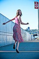 Woman running down sidewalk, rear view