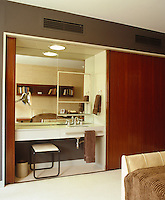 The bedroom features a built-in dressing table and wash basin next to the wardrobe which can be concealed behind sliding wooden doors