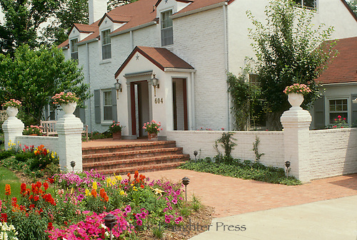 Formal antique white brick home with entrance and blooming gardens