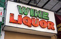 """A liquor store displays their """"Wine Liquor"""" neon sign in the Chelsea neighborhood of New York on Friday, April 17, 2015. (© Richard B. Levine)"""