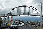 Children ride bikes across bridge over road outside Quito, Equador