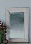 A mirror sits on a mantel.