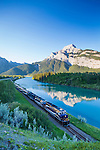The Rocky Mountaineer passenger train as seen at dawn near Exshaw, Alberta, Canada, with Heart Mountain reflected in the Bow River