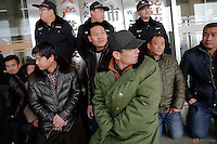 Migrant workers sit in front of policemen as they protest in front of a local government office in Qianan, Tangshan City, Hebei province, China January 28, 2016. REUTERS/Damir Sagolj