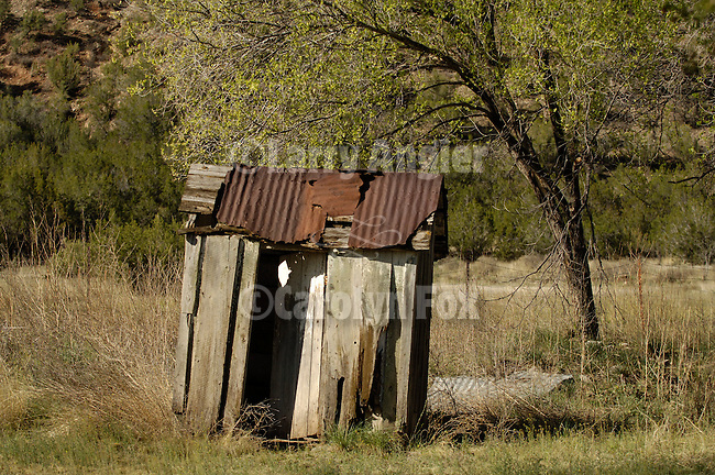 Weathered, leaning outhouse, rusting roof, New Mexico