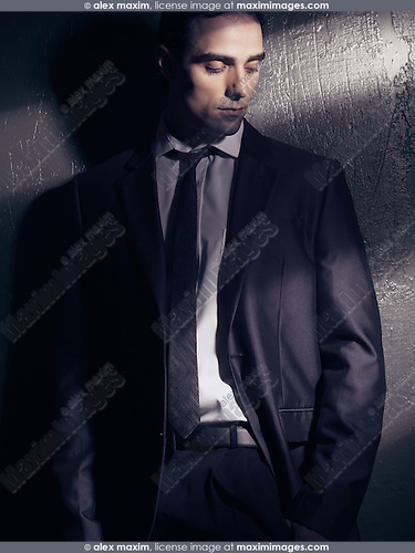 Artistic expressive portrait of a young man wearing a business suit standing looking down in dim dramatic light