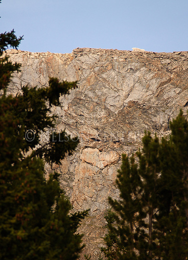 cracks in the rocks of a rocky cliff form a heart shape above september morn lake in the beartooth wilderness