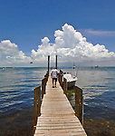 Man walks toward a small boat down a wooden dock that opens out onto dramatic sky over Blackwater Sound in Key Largo