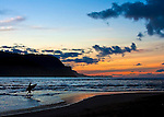 A lone surfer heads home in the sunset on Ke'e Beach at Hanalei Bay on the island of Kaua'i, Hawaii.