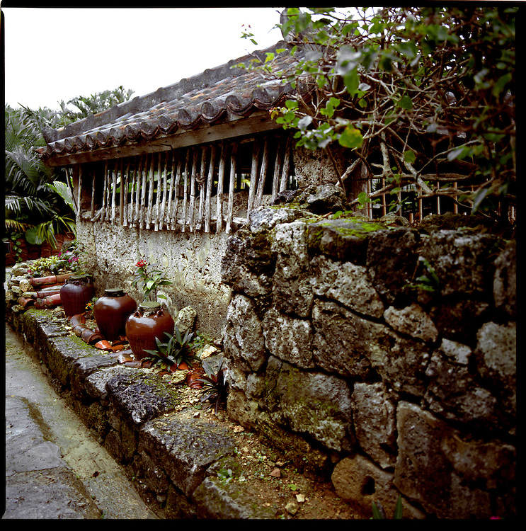 Coral stone walls and red terra-cotta water vessels outside a traditional Okinawan house, Ryukyu Mura, Okinawa, Japan.