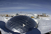 The geodesic dome at Amundsen Scott South Pole Station is seen on Jan. 5, 2001. It has been dismantled and replaced by the new station, seen under construction in the background. Ernie Mastroianni photo