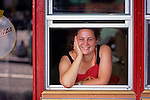 "Young woman working at a pizza place along the ""Ave"" smiling leaning on ordering window sill University District Seattle Washington State USA"