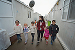 """Teacher Spearans Yoqresh Marogil walks children home after they spent time in a church-sponsored """"child-friendly space"""" in the village of Bakhtme, Iraq, which was flooded with displaced families when the Islamic State group took over nearby portions of the Nineveh Plains in 2014. Many of the displaced families live in """"caravans,""""  the manufactured housing units through which they walk. The children's space is sponsored by the Christian Aid Program Nohadra - Iraq (CAPNI), and includes some children from the host community as well."""