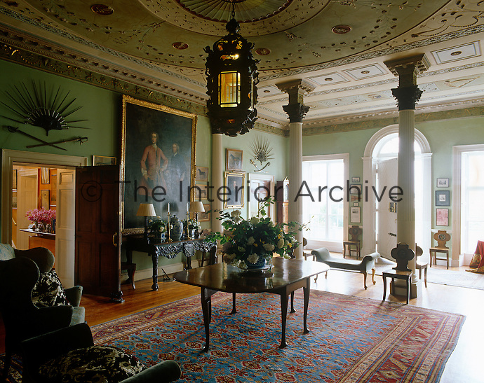 The entrance hall at Glin Castle is furnished with important Irish pieces and has an ornate plaster ceiling