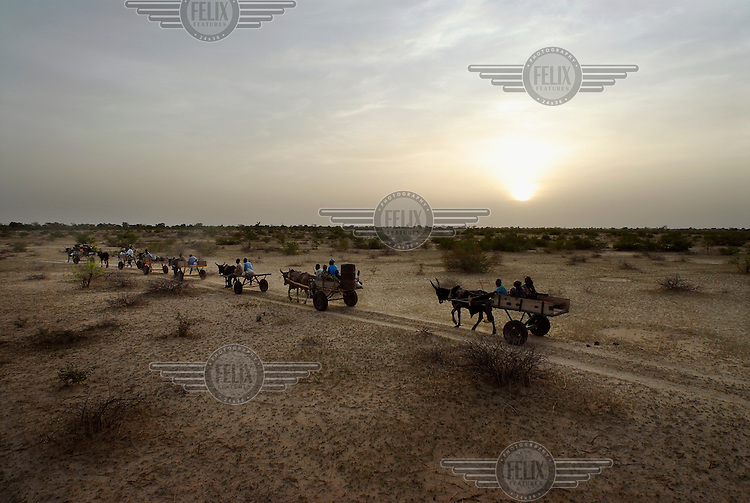 Traders from the dry sub-Saharan Sahel region drive their carts home at the end of market day in Aguie.