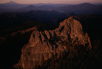 Pilot Rock a plug of volcanic basalt juts 400 feet above Cascade Siskiyou National Monument, a crossroads of mountain ranges, geological eras, and habitats in southern Oregon. The 65,000 acre monument is at the junction of the Oregon and Cascades and Siskiyou Mountains with Mt. shasta rising in the far distance, across the state line in California.