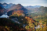 Colorful autumn trees cover mountains surrounding Hohechwangau, Allgaeu, Bavaria, Germany