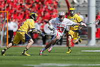 Ohio State's Kacy Kapinos (33) takes the ball down field under pressure from Michigan's David McCormack (5) in the first quarter of the NCAA lacrosse game between the Ohio State Buckeyes and Michigan Wolverines at Ohio Stadium in Columbus, Saturday morning, April 12, 2014. The Ohio State Buckeyes defeated the Michigan Wolverines 15 - 6. (The Columbus Dispatch / Eamon Queeney)