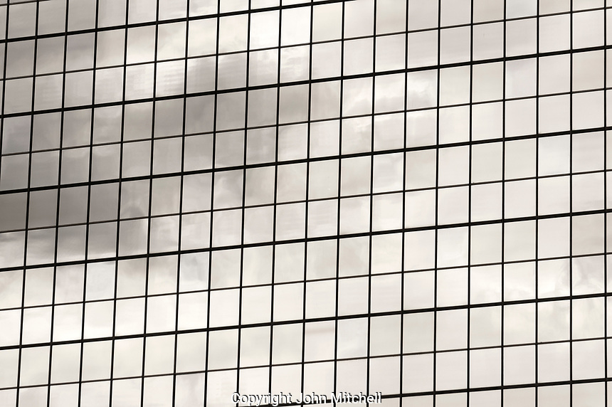 Black and white image of a grid pattern on the facade of a glass office building, Vancouver, BC, Canada
