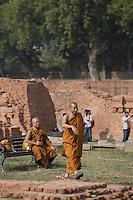 Buddhist monks at Dhamek Stupa monument one of four pilgrimage sites designated by Siddhartha Gautama Buddha<br /> Sarnath, varanasi, Uttar Pradesh, India