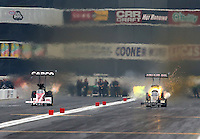 Feb 9, 2014; Pomona, CA, USA; NHRA top fuel dragster driver Terry McMillen (right) blows a head gasket racing alongside Steve Torrence during the Winternationals at Auto Club Raceway at Pomona. Mandatory Credit: Mark J. Rebilas-