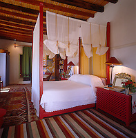 Large patterned rugs on the traditional tiled floor make this red-painted bedroom cosy under-foot