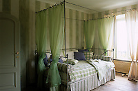 Sheer green curtains frame an iron four-poster bed in this green and white striped bedroom