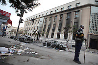 A man from neighborhood watch stands guard in an area of downtown Cairo destroyed after protesters clashed with police on the previous day.