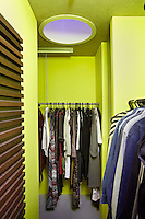 A walk-in wardrobe decorated in a bold, fluorescent yellow. Metal rods provide plenty of hanging space for clothes.