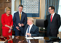 United States President Donald J. Trump hands the pen he used to sign the second of three Executive Orders concerning financial services to US Senator David Perdue (Republican of Georgia) at the Department of the Treasury in Washington, DC on April 21, 2017.  From left to right: US Representative Claudia Tenney (Republican of New York) Senator Perdue, the President, and US Secretary of the Treasury Steven Mnuchin.<br /> Credit: Ron Sachs / Pool via CNP /MediaPunch