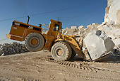 Tractor loading a marble block in a quarry, Carrara, Alpi Apuane, Italy