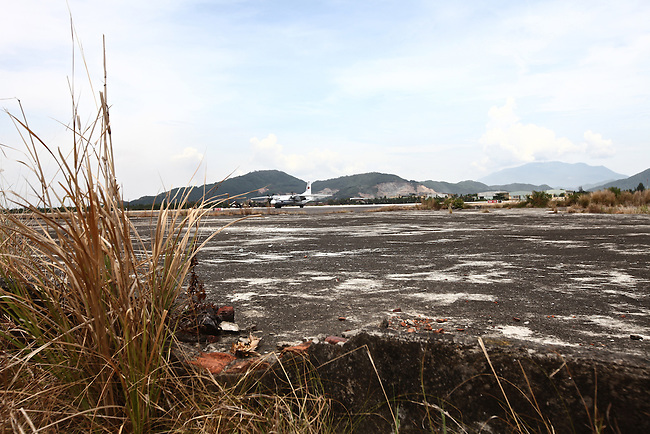 """A plane taxis on the runway near the former herbicide storage and loading ramp at the international airport in Da Nang, Vietnam. The airport served as a major U.S. base and storage site for Agent Orange and other herbicides during the Vietnam War more than 40 years ago, and is still heavily contaminated with dioxin, a deadly compound that has been linked to cancer, diabetes, birth defects and other serious illnesses. The United States is paying to clean up contaminated soil at the airport, a $43 million project that started last August and is expected to take until the end of 2016 to complete. But there are at least 26 other known or potential dioxin """"hotspots"""" in Vietnam, all of them around former U.S. bases. It is unclear at this point how or when these sites will be cleaned up and who will pay for it. May 30, 2012."""
