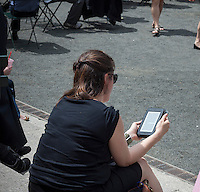 A visitor to Bryant Park in New York uses her Nook e-reader on Friday, May 10, 2013. Microsoft is condiering acquiring the Nook Media unit from Barnes & Noble. (© Richard B. Levine)