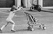 Young girl pushing her buggy, Wester Hailes, Scotland, 1979.  John Walmsley was Photographer in Residence at the Education Centre for three weeks in 1979.  The Education Centre was, at the time, Scotland's largest purpose built community High School open all day every day for all ages from primary to adults.  The town of Wester Hailes, a few miles to the south west of Edinburgh, was built in the early 1970s mostly of blocks of flats and high rises.