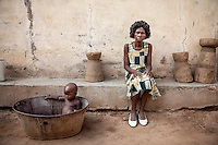 Traditional healer Elena Jakson outside her house with her one year old granddaughter Marbel sitting in a tin bath beside her.