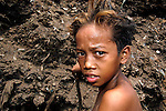 """A decade after it was closed, children like this boy continue to scavenge in """"Smokey Mountain"""", an infamous Manila dumpsite. They are searching for items of value, including plastic, glass and metal, that can be recycled..."""