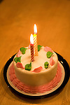 A birthday cake decorated in pink and green iceing and two lit candles sits on a table.