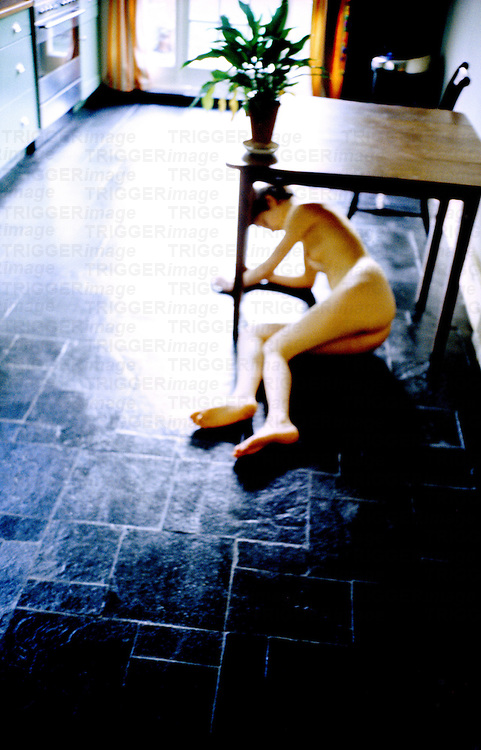 A naked young woman lying under a kitchen table
