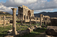 Atrium of the House of Ephebe with its courtyard lined with columns with Corinthian capitals, and behind, the Triumphal Arch of Caracalla, built 217 AD by the city's governor Marcus Aurelius Sebastenus in honour of Emperor Caracalla, 188-217 AD, and his mother Julia Domna, and the Basilica, 217 AD in the distance, Volubilis, Northern Morocco. Volubilis was founded in the 3rd century BC by the Phoenicians and was a Roman settlement from the 1st century AD. Volubilis was a thriving Roman olive growing town until 280 AD and was settled until the 11th century. The buildings were largely destroyed by an earthquake in the 18th century and have since been excavated and partly restored. Volubilis was listed as a UNESCO World Heritage Site in 1997. Picture by Manuel Cohen
